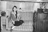 Old photo of a woman relaxing on her vintage trailer's couch with her cat, at the Project Hanford Trailer City in Washington