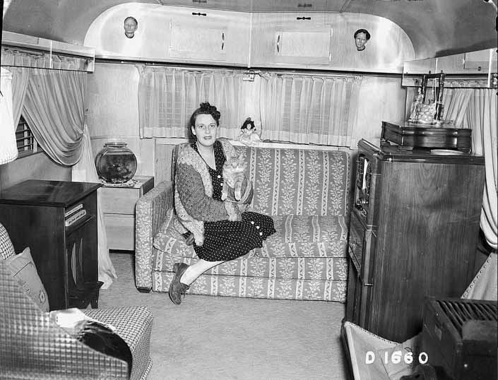 Government photo shows a woman relaxing on her trailer's couch with her cat, at the Project Hanford Trailer City in Washington
