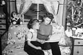 Vintage photo of a mother reading to her son next to the Christmas tree in a vintage trailer, at the Project Hanford Trailer City in Washington