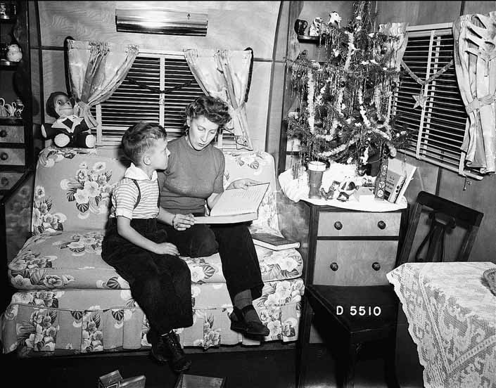 Government photo shows a mother reading to her son next to the Christmas tree in a vintage trailer, at the Project Hanford Trailer City in Washington