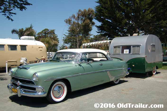 This vintage towing rig is a hudson hollywood 2-door hardtop pulling a vintage travel trailer