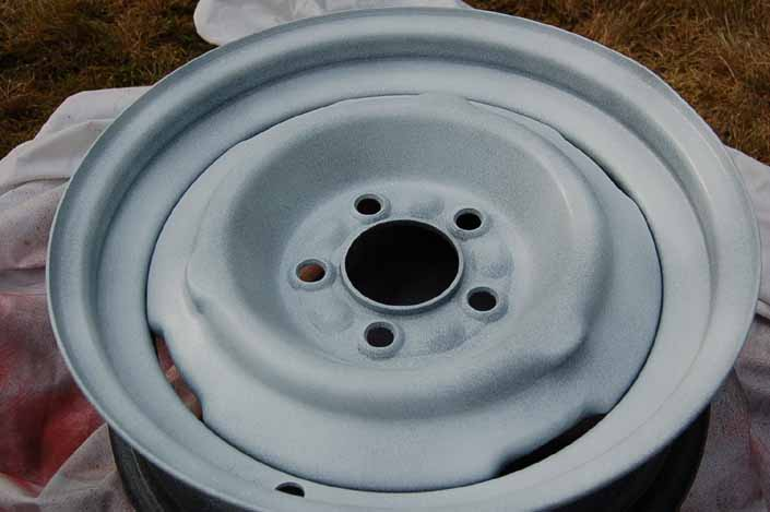 Photo shows the trailer wheel after the first 2 coats of gloss finish paint have been sprayed on