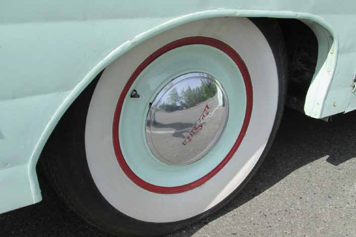 Photo shows an example of a vintage trailer with wheels that have a unique painted full hubcap and wide ww tires