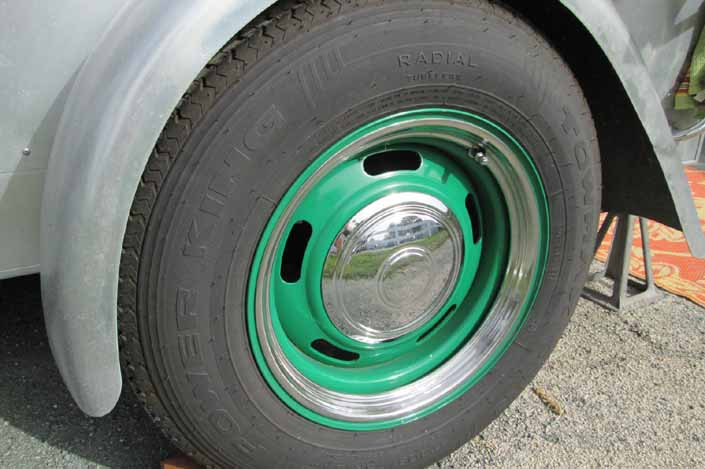 Photo shows an example of a vintage trailer with wheels painted green, with chrome hubcaps and beauty rings
