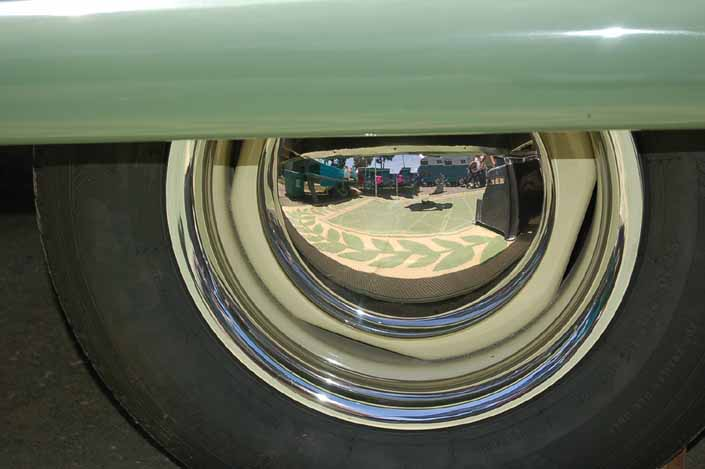 This image shows an example of vintage trailer wheels painted cream yellow, with chrome hubcaps and beauty rings