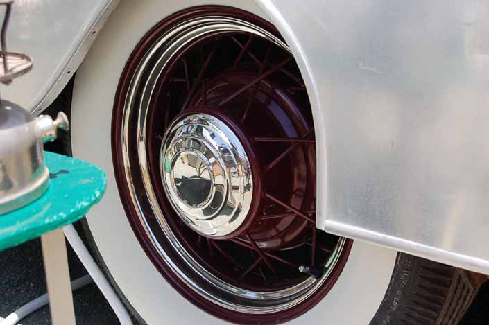 This image shows an example of vintage trailer wire wheels painted maroon, with small chrome hubcaps and beauty rings