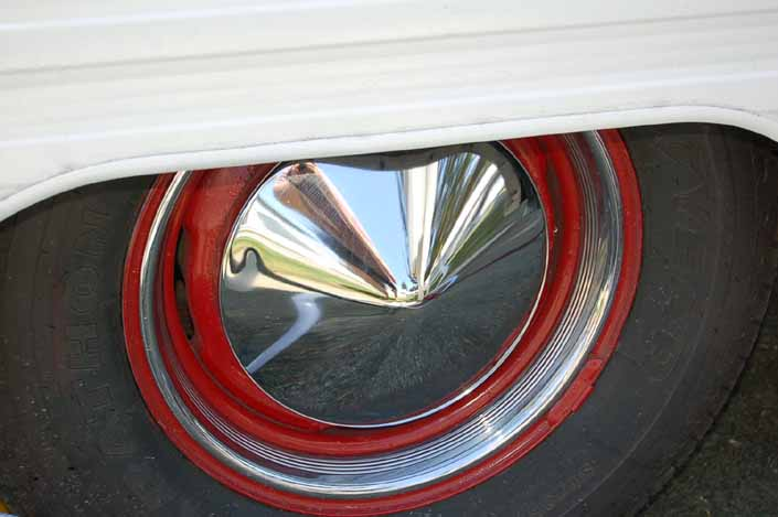 Image is an example of a vintage trailer wheel painted red and with a pointy chrome hubcap and beauty ring