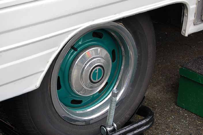 This example shows what vintage trailer wheels painted green look like with chrome hubcaps and beauty rings
