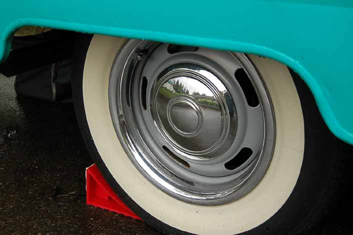 Photo shows an example of a vintage trailer with wheels painted silver, with chrome hubcaps, beauty rings and wide ww tires