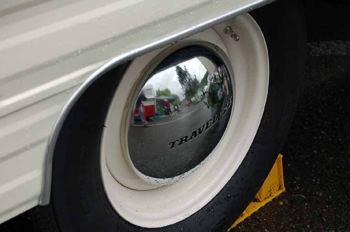Photo shows an example of a vintage trailer with wheels painted white, with chrome hubcaps