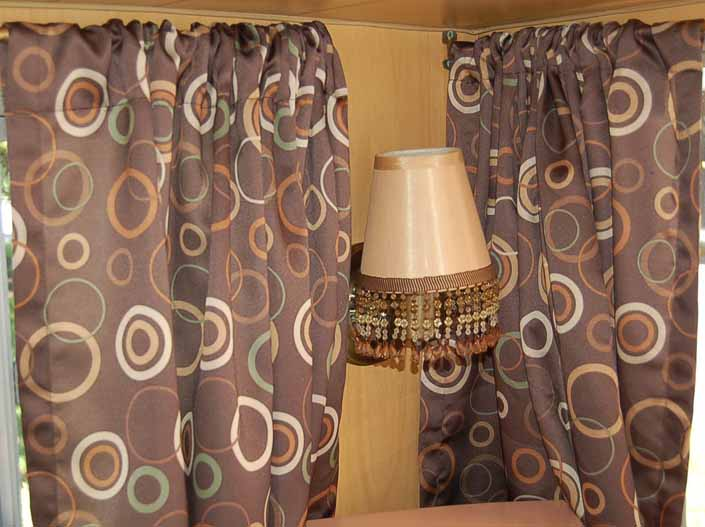 This photo shows a swatch of retro fabric with a 1960's circles graphics pattern on a brown background, for your vintage trailer