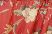 This photo shows a swatch of retro fabric with a tropical flowers pattern on a red background, for your vintage trailer