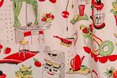 This photo shows a swatch of retro fabric with a cheerful kitchen appliances illustrations pattern, for your vintage trailer