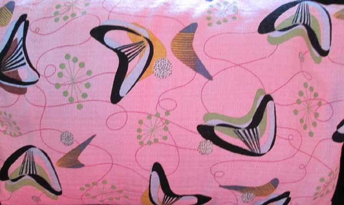 This photo shows a swatch of retro fabric with a Googie boomerangs design on a pink background, for your vintage trailer