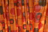 This photo shows a swatch of retro fabric with a mid-century geometrics pattern on an orange background, for your vintage trailer