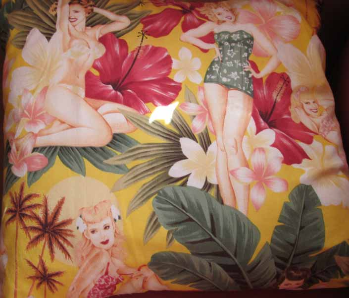 This photo shows a swatch of retro fabric with dreamy pinup girls in a tropical paradise, for your vintage trailer