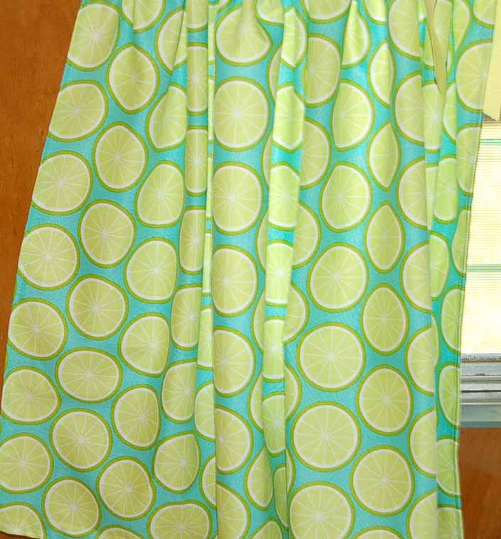 This photo shows a swatch of retro fabric with a 1960's colorful lemon slices design, for your vintage trailer