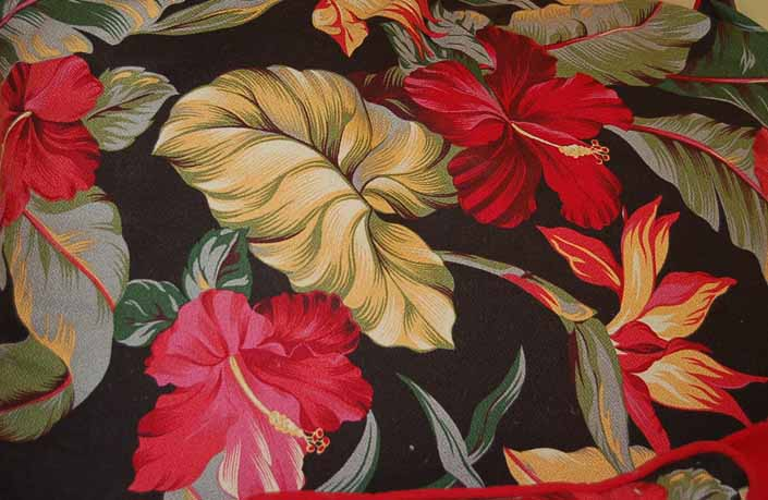 This photo shows a swatch of retro fabric with Hawaiian Flowers on a black background, for your vintage trailer