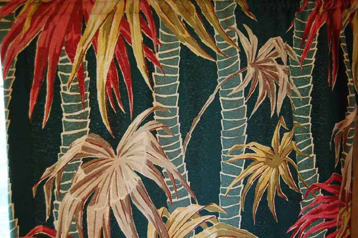This photo shows a swatch of retro fabric with a vintage bamboo and tropical flowers pattern, for your vintage trailer