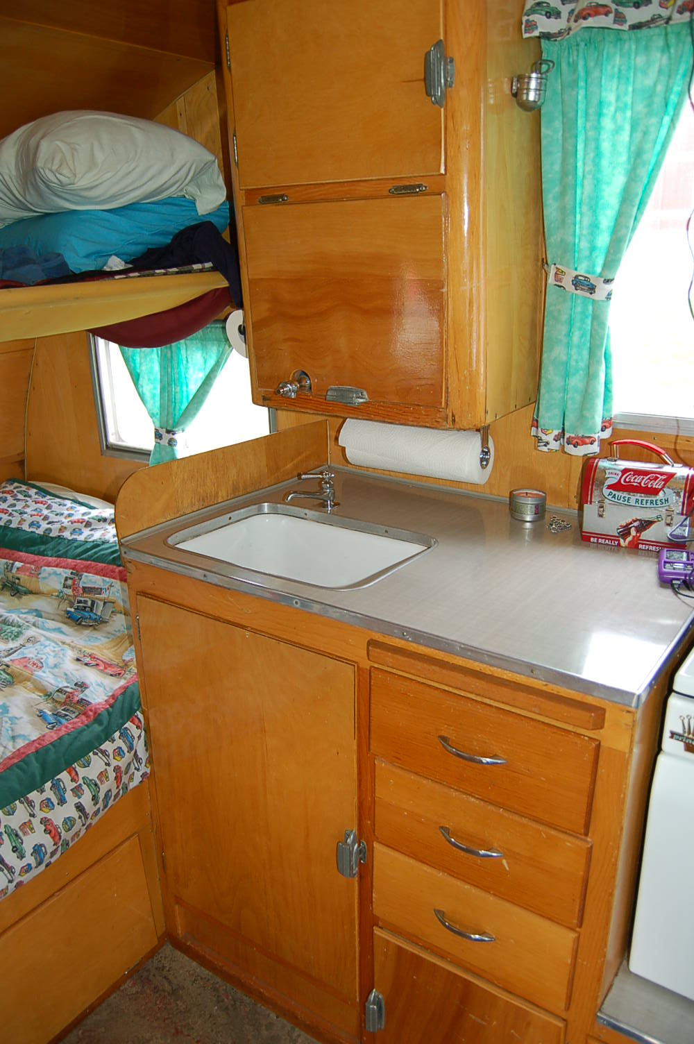 Cabinets with warm honey gold finish in vintage shasta 1500 trailer