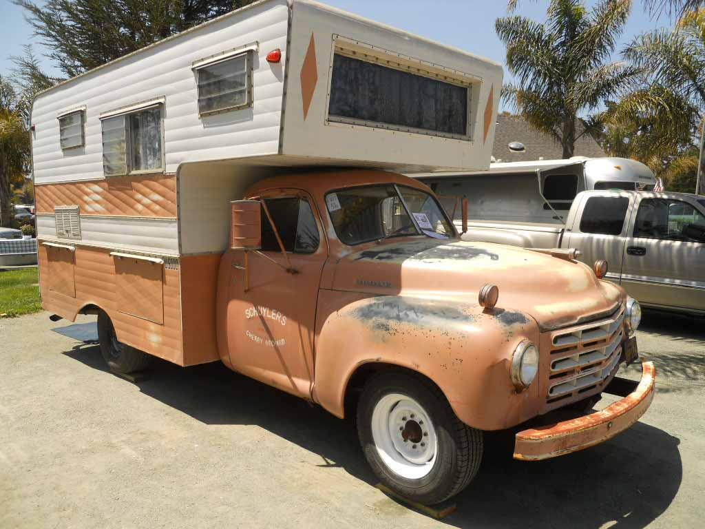 Classic studebaker pickup truck with a vintage camper shell mounted in the bed