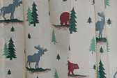 This photo shows a swatch of retro fabric with a moose, bear and woodsy cabin pattern, for your vintage trailer