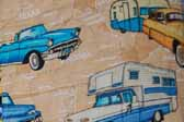This photo shows a swatch of retro fabric with a vintage trailers, cars and pickup trucks pattern