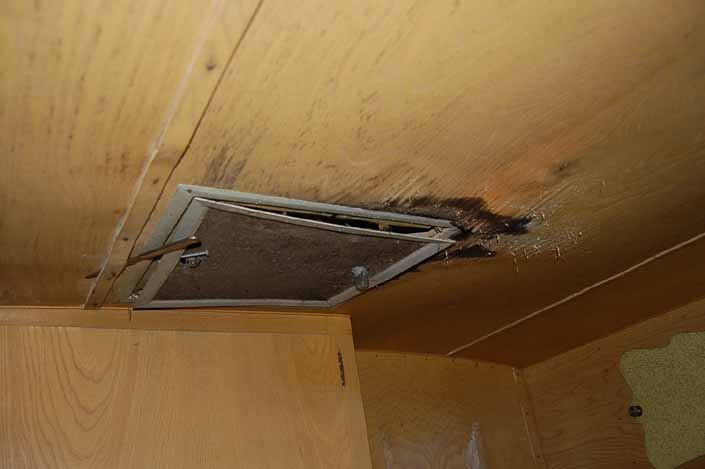 Water damaged ceiling paneling in vintage Shasta trailer in storage yard