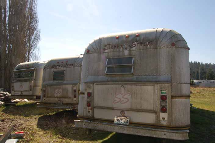 Vintage trailer junkyard has a row of Silver Streak trailers with the standard Silver Streak large rear bumper