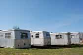 Photo provides a rear end view of a group of Spartan Manor trailers parked in a vintage trailer junkyard