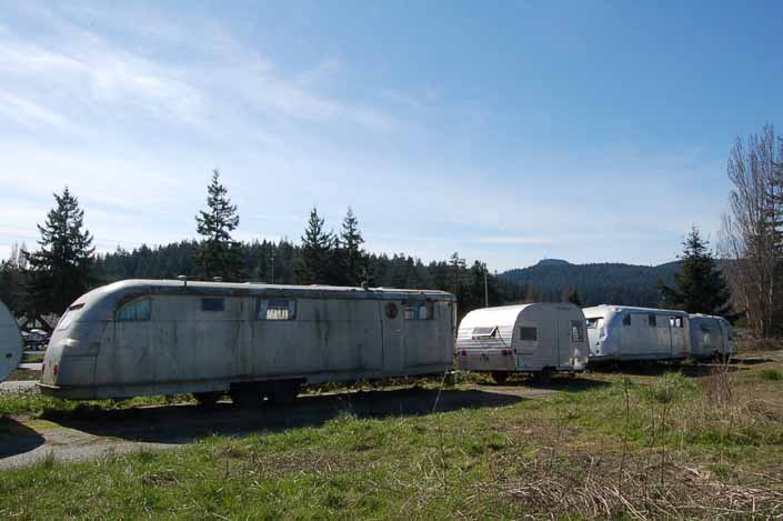 Row of Vintage travel trailers stored at a vintage trailer junkyard and awaiting restoration