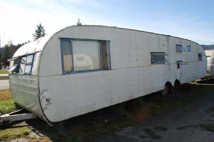 Vintage trailer junk yard has a long vintage Traveleze trailer in need of restoration