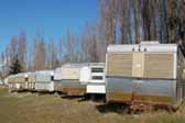 Pictures shows a row of classic Silver Streak trailers parked in a Vintage Trailer Storage-Yard