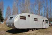 Vintage Spartanette travel trailer parked in a storage yard and perfect for restoration