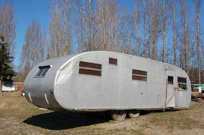 Vintage trailer junk yard has a restorable vintage Spartanette trailer in storage