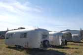 Picture of a group of vintage aluminum Airstream-style travel trailers in a trailer storage yard