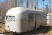 Photo of a vintage aircraft styled trailer stored in an old junkyard and ready to be restored