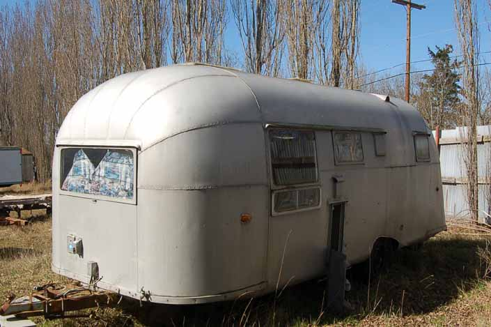 Vintage trailer junk yard has a restorable vintage aircraft-styled aluminum trailer in storage
