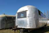 Classic Airstream trailer with dents is parked in a vintage trailer storage yard