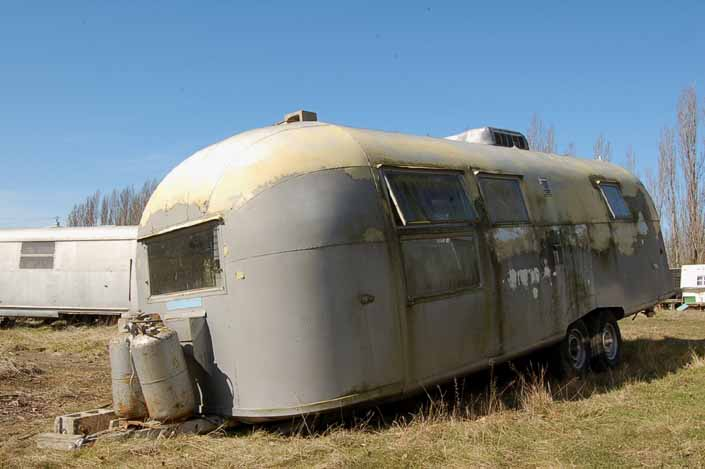 Vintage trailer junk yard has a painted Airstream trailer for restoration