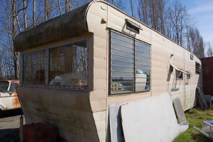 Vintage trailer junkyard has a vintage travel trailer with surface moss but ready for restoration
