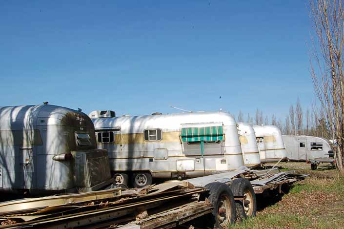 Vintage trailer junk yard has a torn-down vintage trailer twin-axle frame with wood floor platform