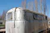 Rear end view shows unique modular side panels on a rare Palace trailer parked in a vintage trailer junkyard and awaiting restoration