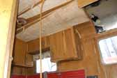 Detail photo shows delaminating but original wood ceiling panels and kitchen cabinets in a Palace trailer stored in a vintage trailer junkyard
