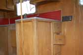 Original wood kitchen cabinets in a rare Palace travel trailer are in restorable condition and stored in a vintage trailer junkyard