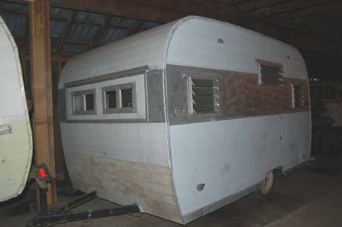 Vintage trailer storage yard has a small vintage Aloha trailer with altered windows, available for restoration
