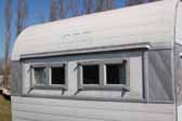 photo shows front windows replaced on an old Aloha trailer in a vintage ttrailer storage-yard