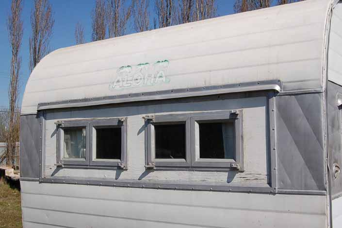 Vintage trailer storage yard has a vintage Aloha trailer with dinette window replaced by smaller front windows, available for restoration