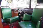 Roomy front cab in custom camper made out of a vintage volkswagen bus, has swiveling captains chairs and original vw dashboard